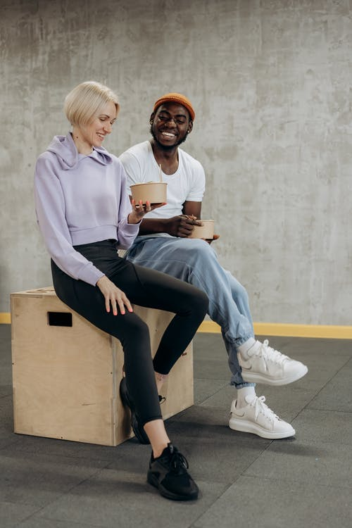 Man And Woman Sitting On A Box With Rice Bowls