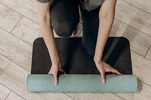 Woman in Black Leggings Unrolling A Yoga Mat