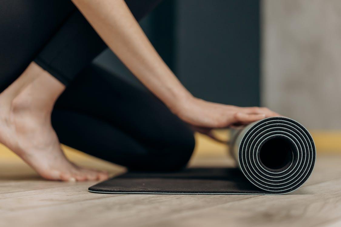 Woman Rolling A Yoga Mat