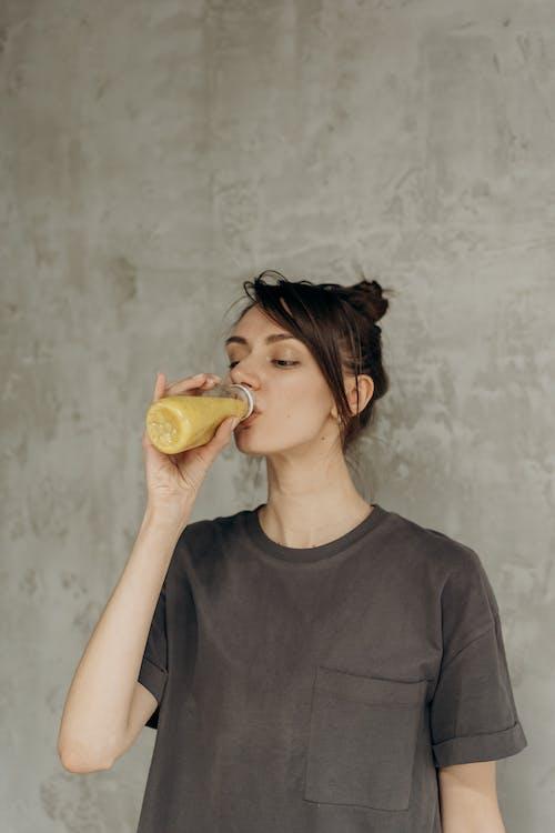 Woman in Black Crew Neck T-shirt Drinking Juice