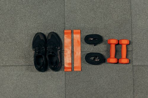 Black Sneakers And Gym Tools on Gray Floor