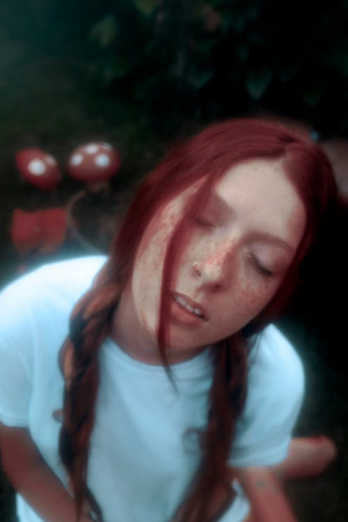 Young dreamy lady in casual clothes with red hair and freckles closing eyes on green grassy lawn in yard in daylight