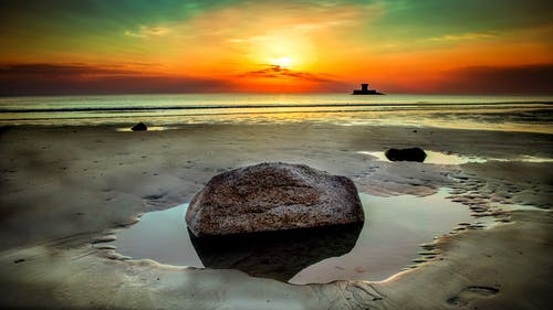 Stone Beside Seashore at Sunset