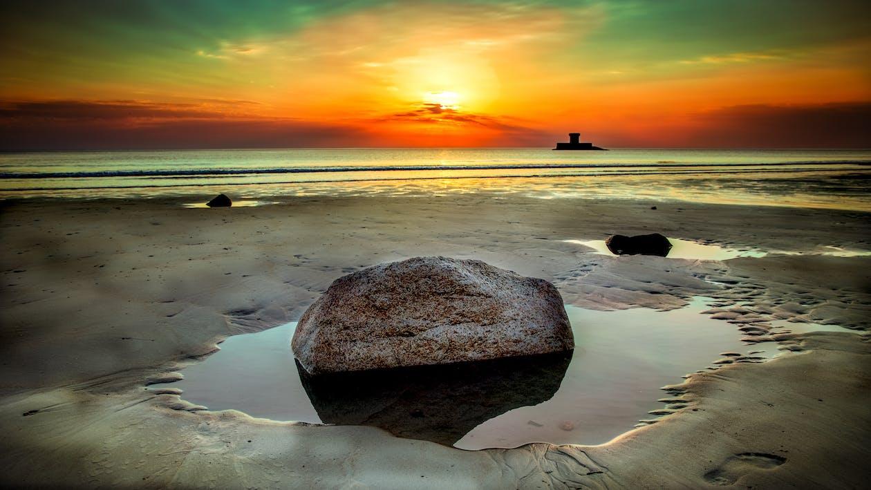 Stone Beside Seashore at Sunset