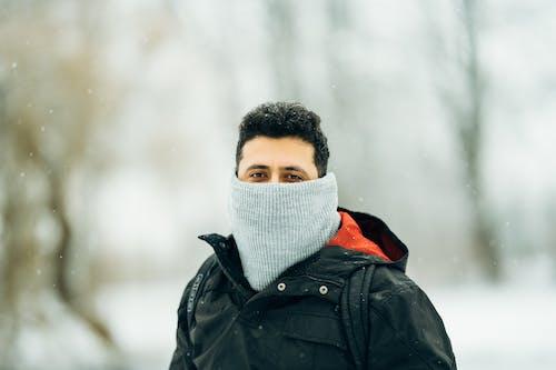 Man in warm outerwear in winter park