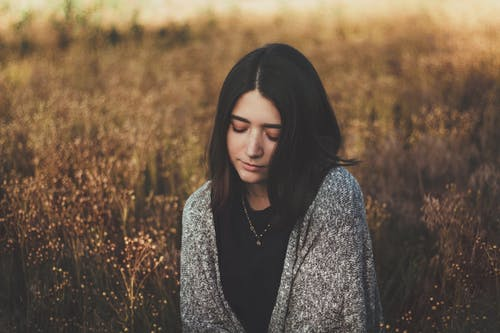 Young woman with dark hair in warm gray sweater standing in field with dry grass in autumn in countryside