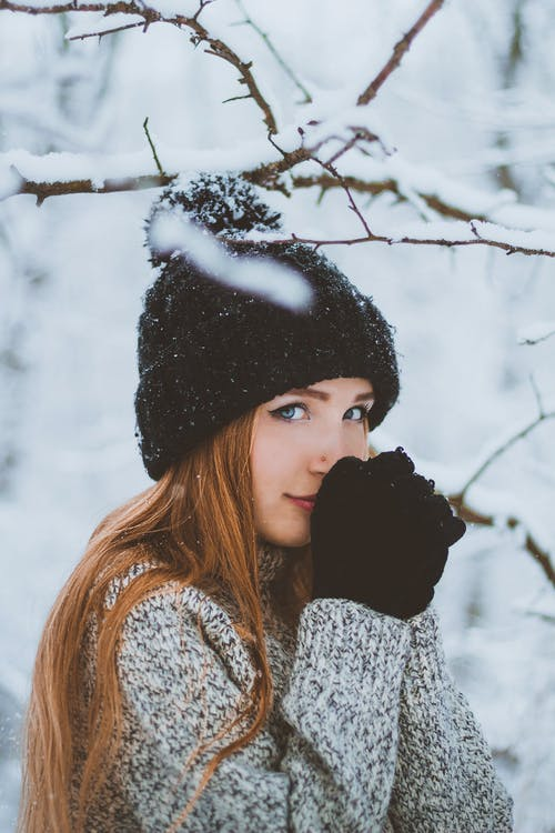 Woman in warm hat gloves and sweater in winter forest