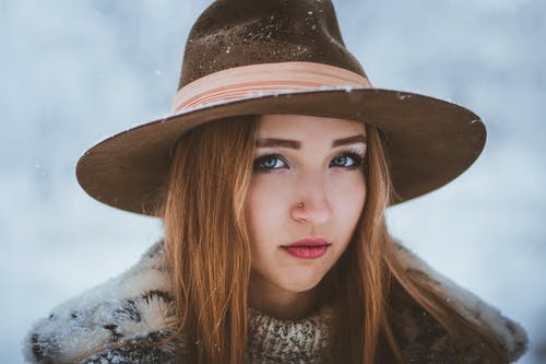 Charming young female wearing trendy hat and warm clothes standing under snowfall and looking at camera