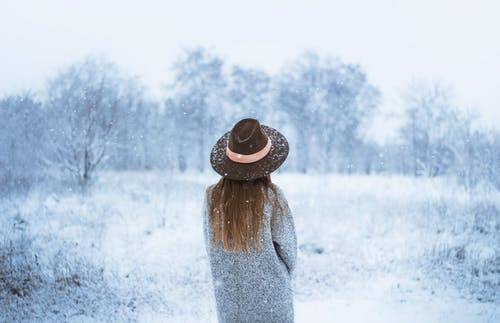 Woman enjoying winter scenery with bare trees under snowfall