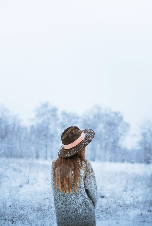 Back view of anonymous female in hat and outerwear standing in snowy valley in haze