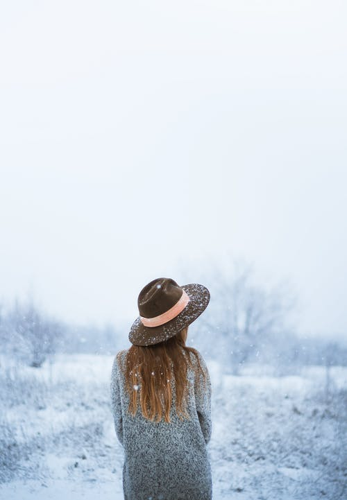 Woman in warm clothes standing in snowy nature