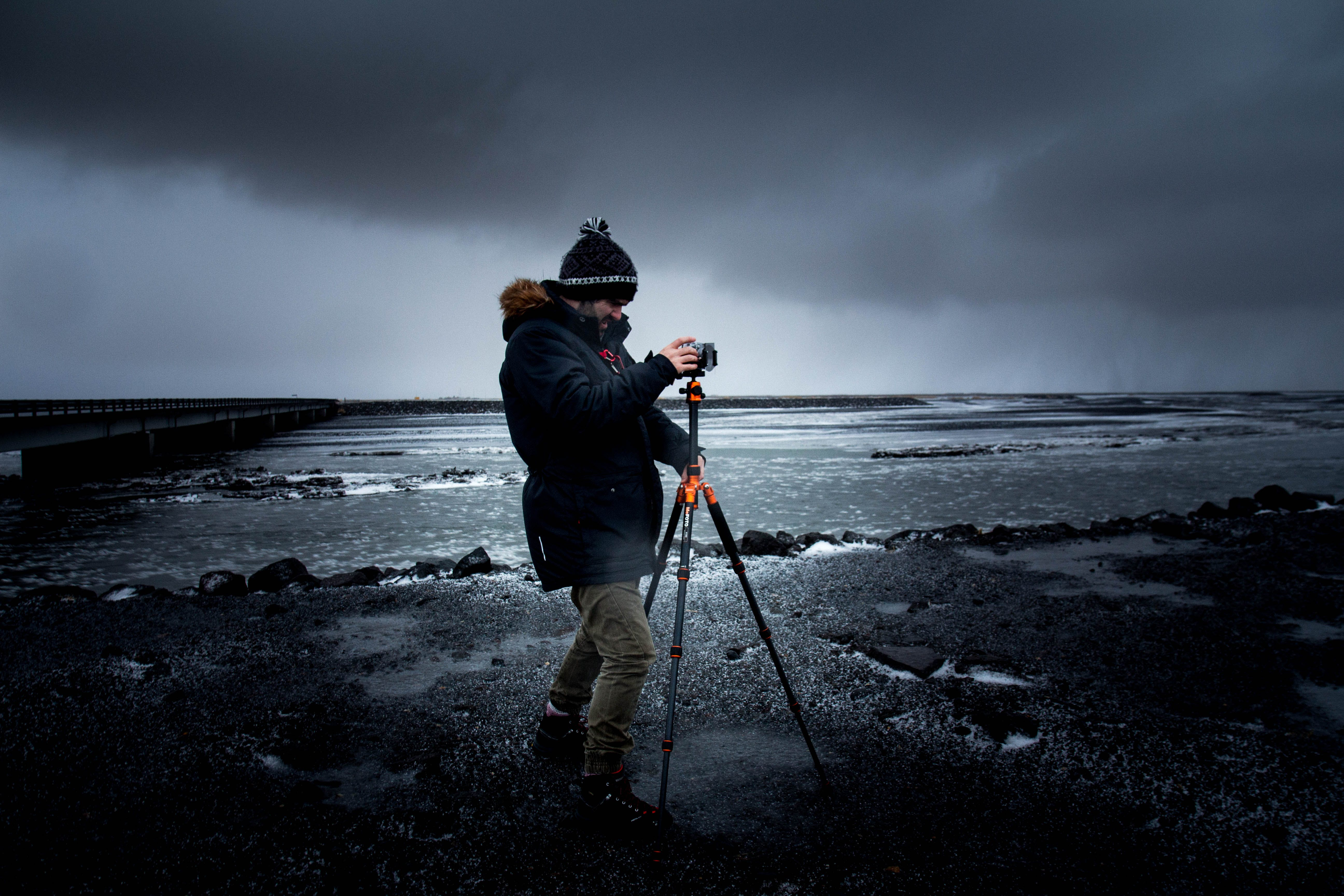 Man in Blue Coat Holding a Tripod With Camera