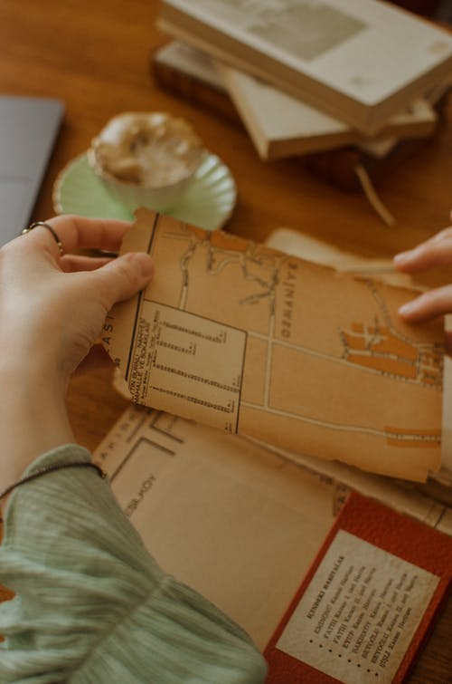 Person Holding Brown Paper Document