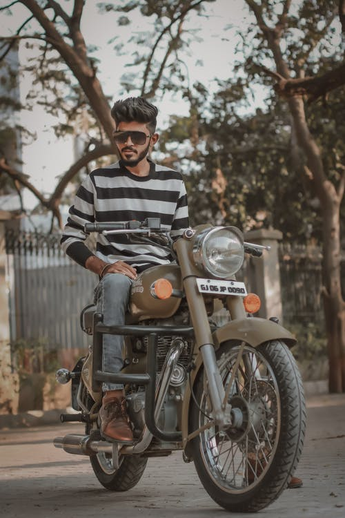 Man in Black and White Striped Long Sleeve Shirt Riding on Motorcycle