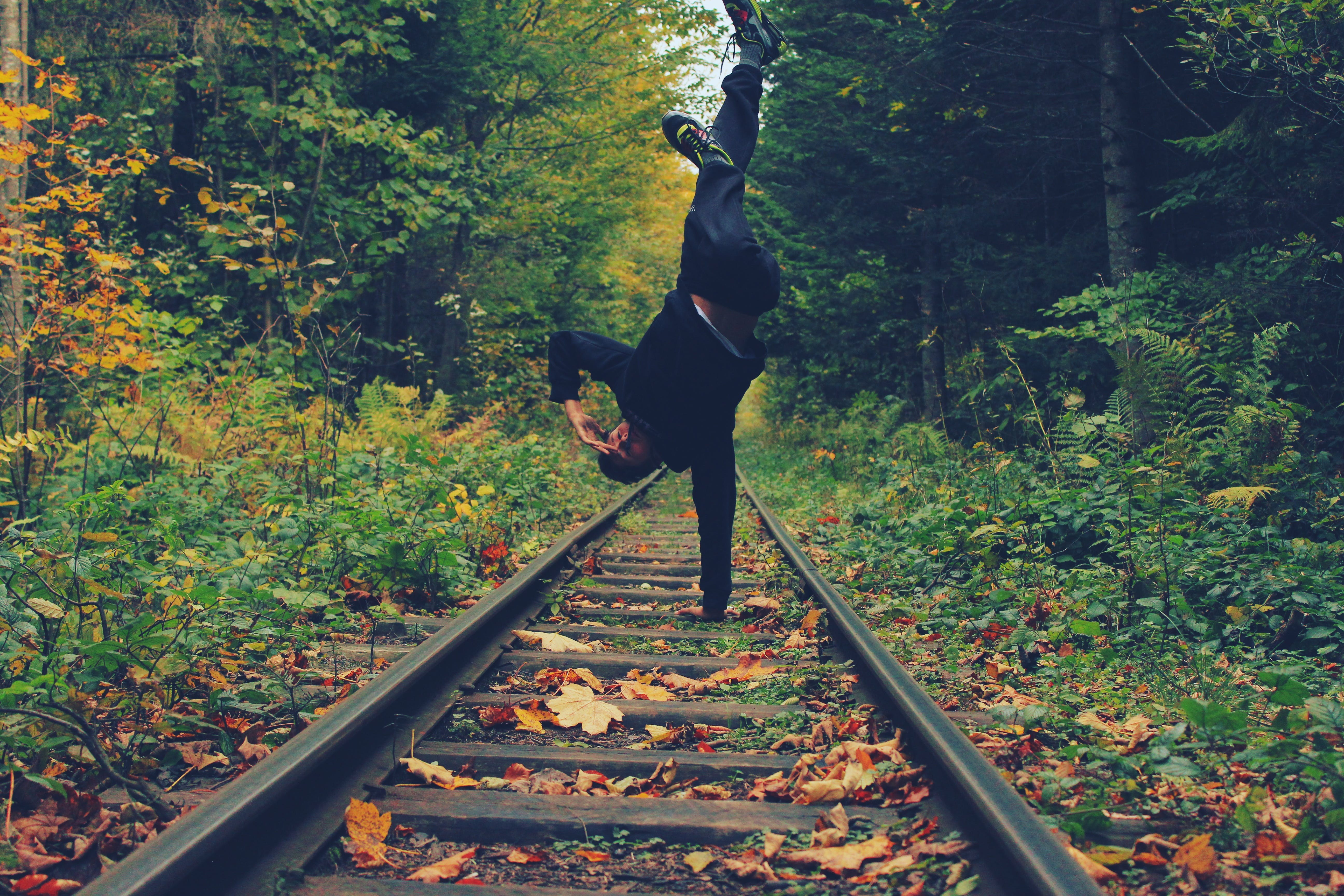 Man Standing With His Right Hand on the Train Rails in Middle of Forest