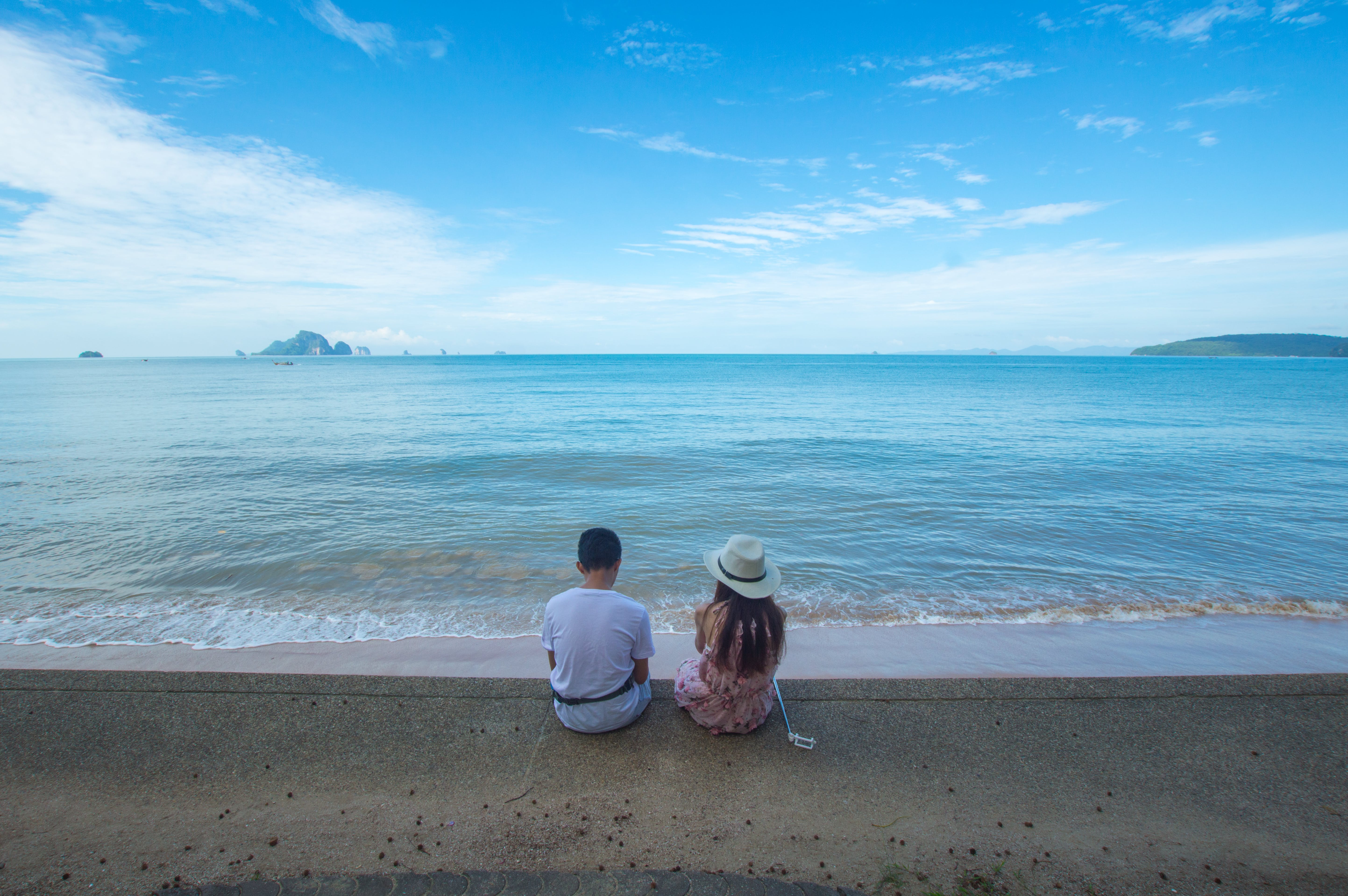 Man and Woman Sitting on Seashore
