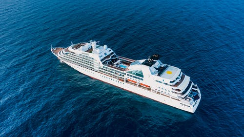 Cruise ship floating on blue sea in sunny day