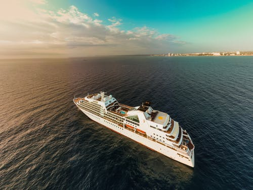 Aerial view of modern white cruise ship sailing on rippling sea water against cloudy sunset sky