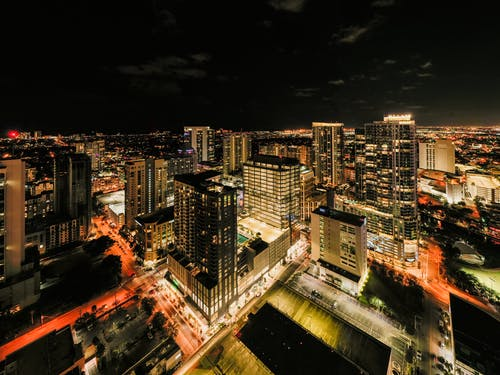 Drone view of illuminated glass skyscrapers in financial district of Fort Lauderdale against night sky