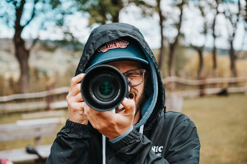 Man in Black Hoodie Taking Photo