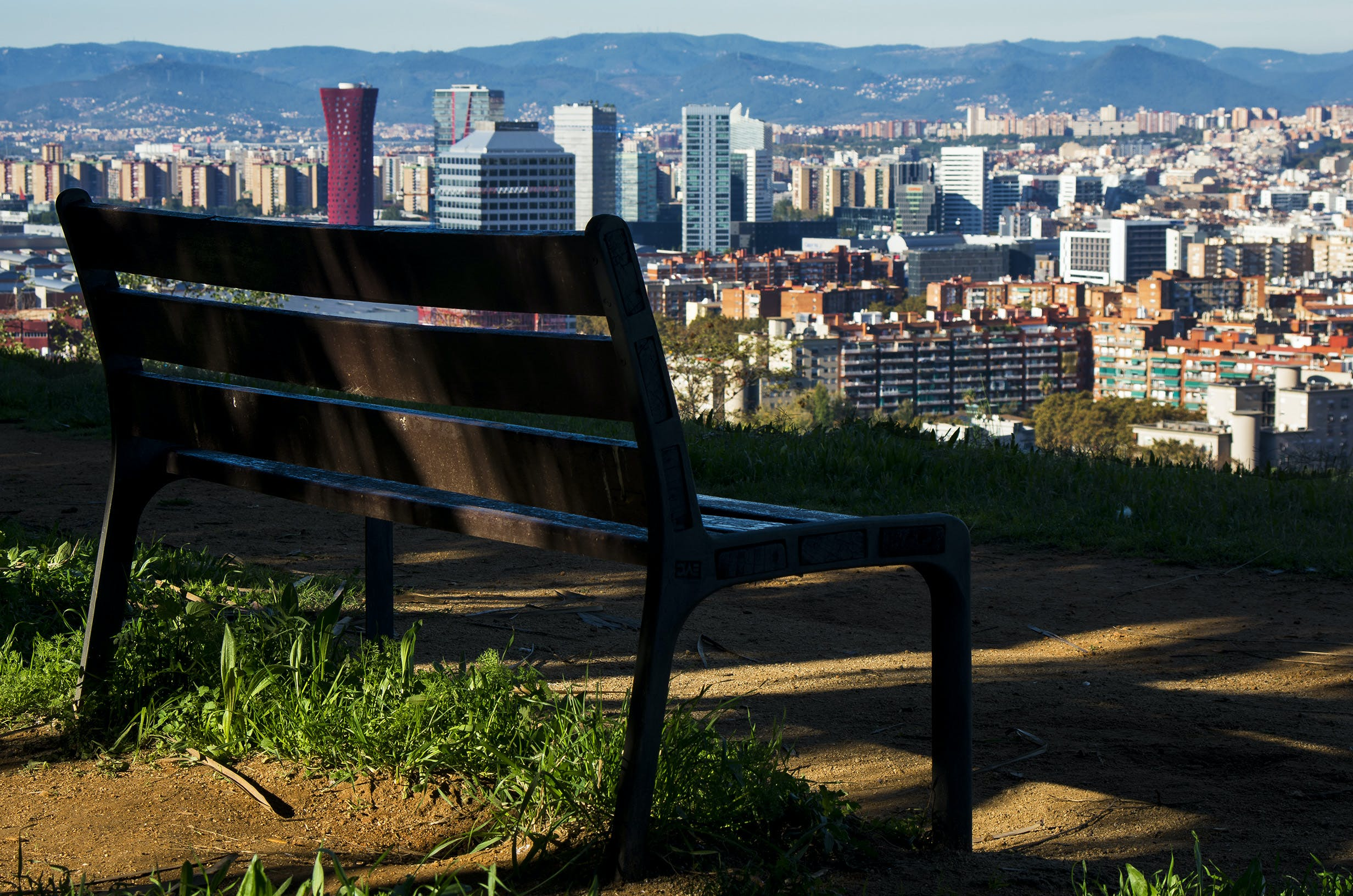 Brown Wooden Bench With Metal Frame Surrounded by Building Scenery