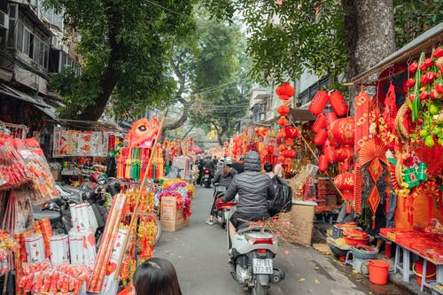 Man in Black Jacket Riding Motorcycle Near Red and White Chinese Lanterns