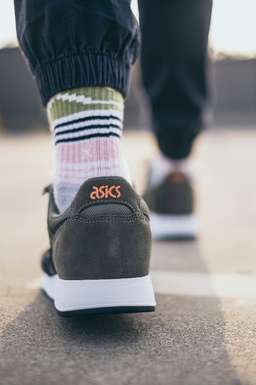 Foot with Gray Asics Rubber Shoes