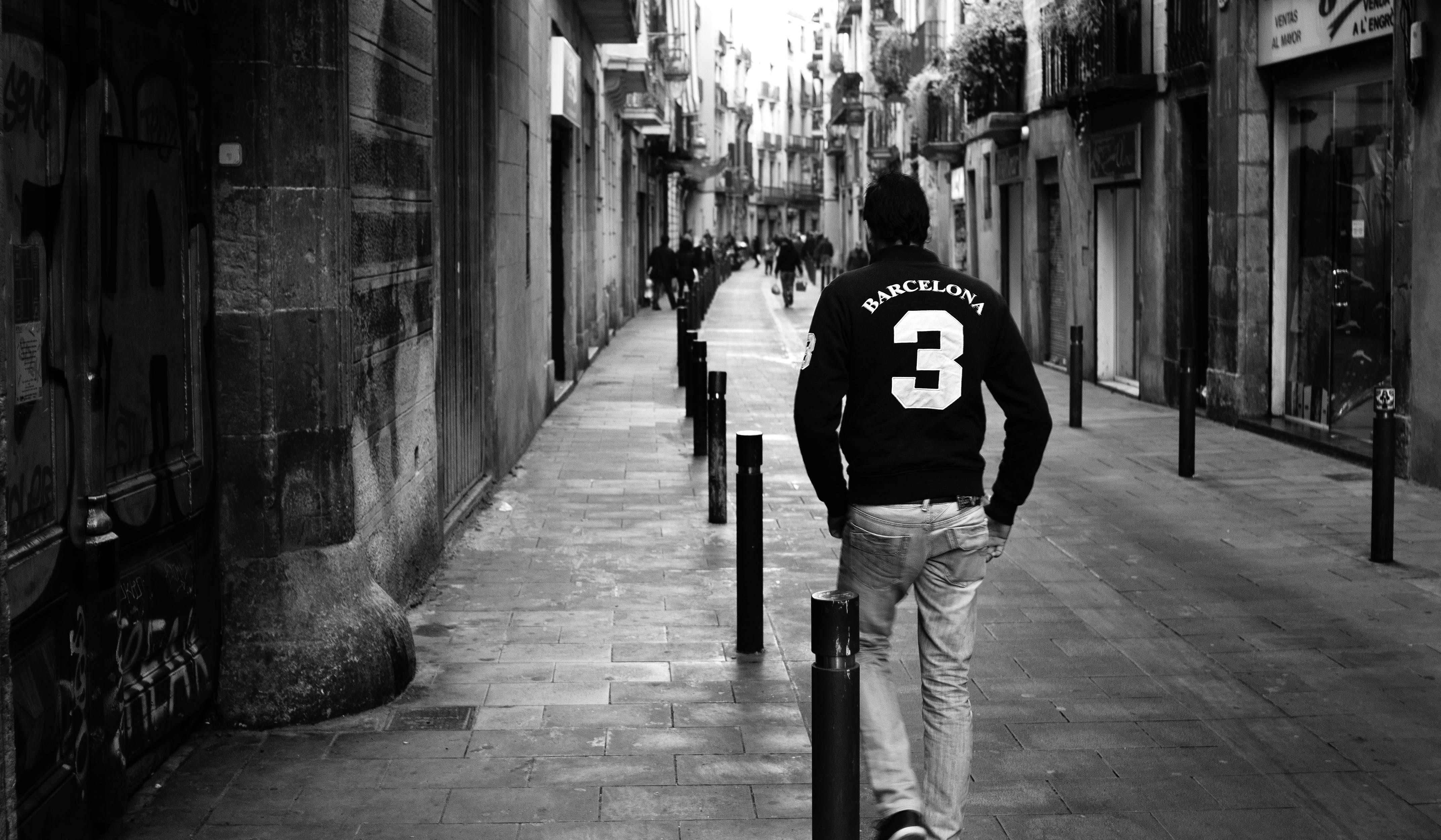 Grayscale Photo of Man Wearing Long-sleeved Shirt and Pants Walking on Concrete Pathway Near Building