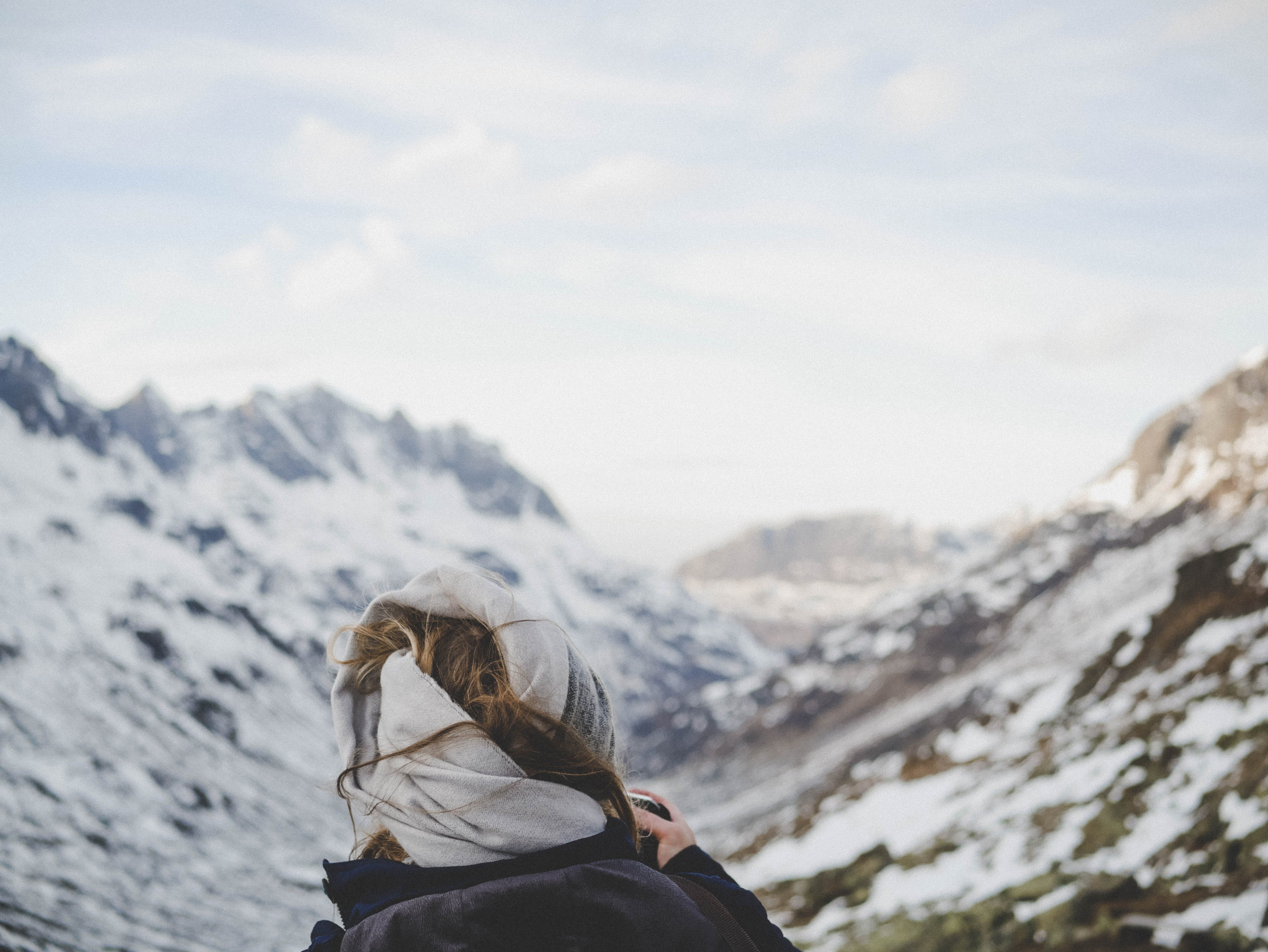 Person Wearing Black Jacket in Front of Mountain Filled With Snow