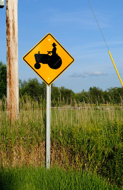 Warning yellow road sign with tractor placed on roadside in lush grassy countryside