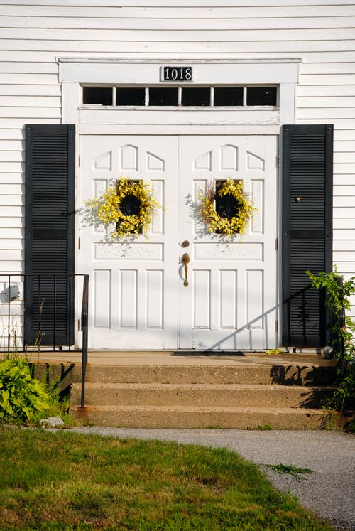Modern cottage entrance doors decorated with yellow flower wreaths in countryside on sunny weather