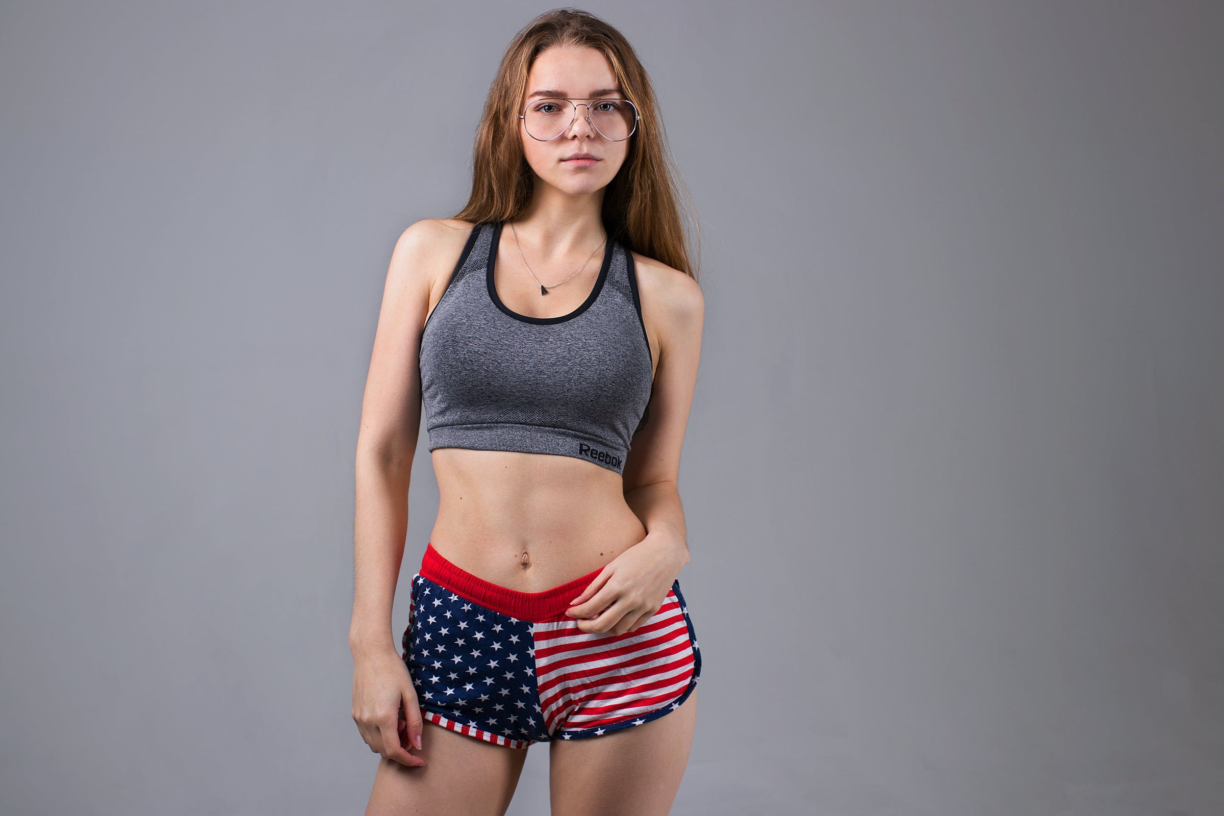 Woman Wearing Grey Sports Bra and U.s. Flag Printed Dolphin Shorts