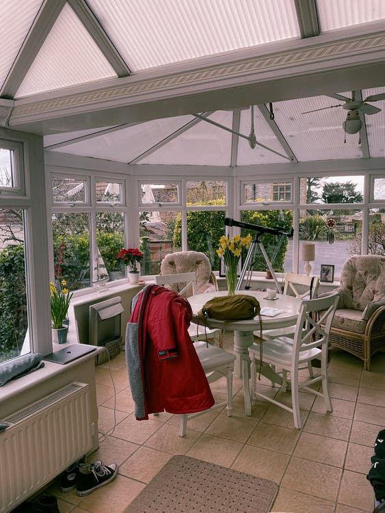 Interior of light house mansard with table and vase of flowers viewing green garden with plants