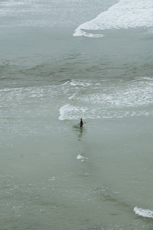 Aerial Shot of a Person Carrying a Surfboard