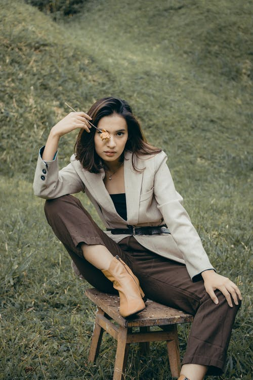 Stylish woman sitting on chair in nature
