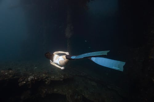 Back view of unrecognizable female traveler in white swimwear and flippers swimming under sea water
