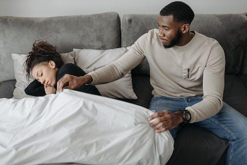 Man Fixing Woman's Blanket