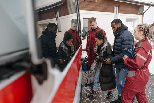 People Helping A Woman Go Inside An Ambulance