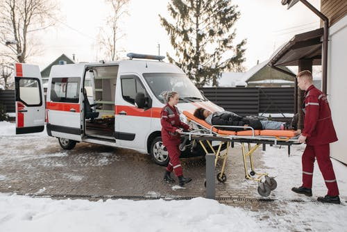 EMT Pushing Woman On A Stretcher
