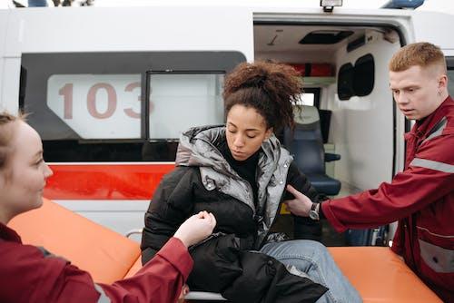 Paramedics Assisting A Woman