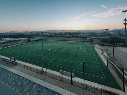 Grassy sports ground in town at sunset