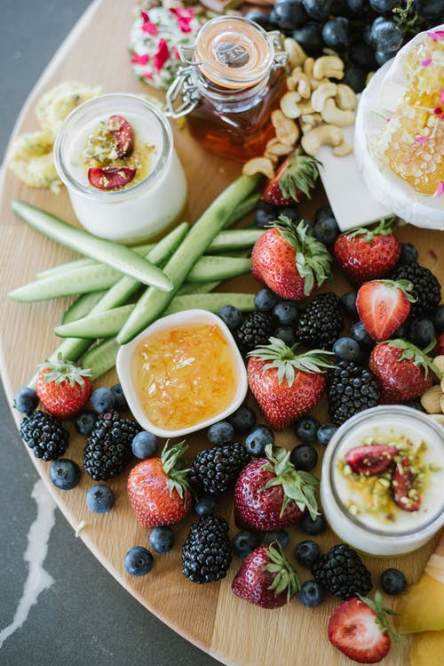 Tray with berries and yogurt near jelly and cucumber slices