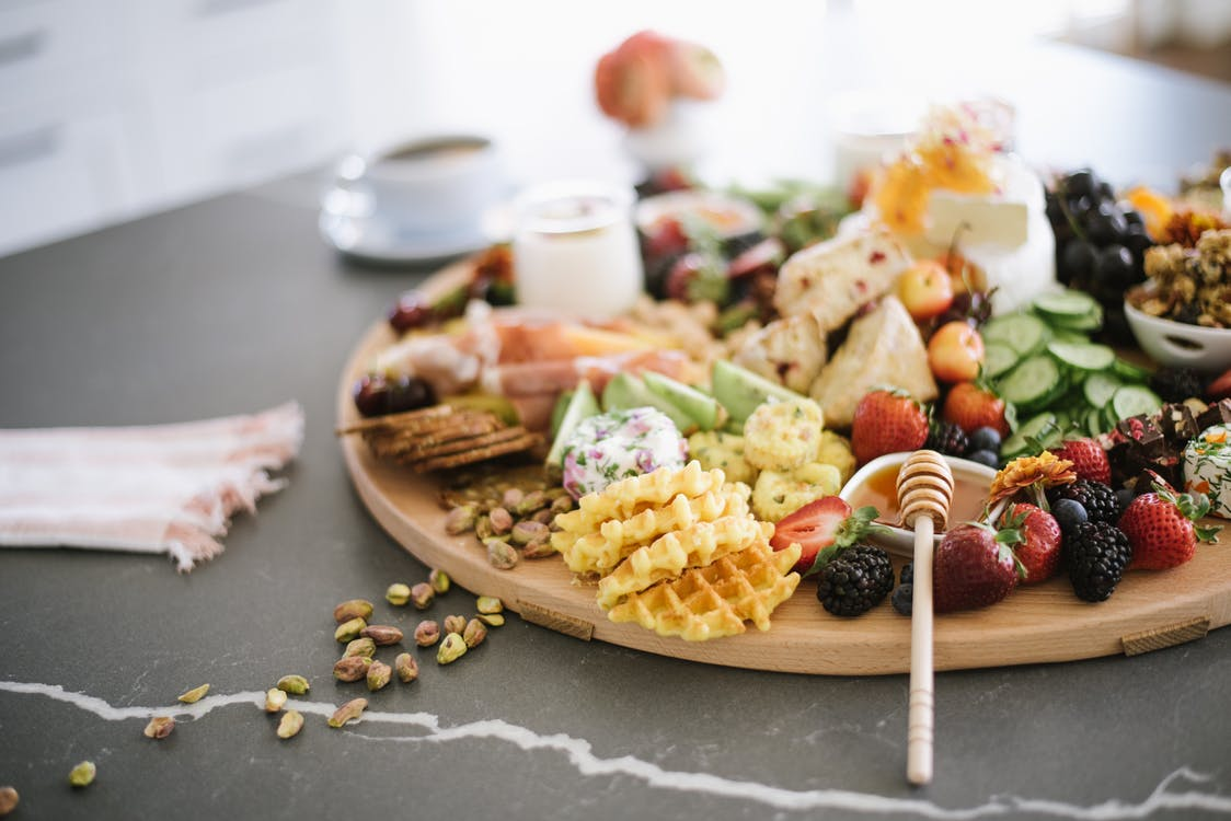 Wooden tray with mixed berries and honey with dipper served with waffles and sweets near cucumber slices on table in light room