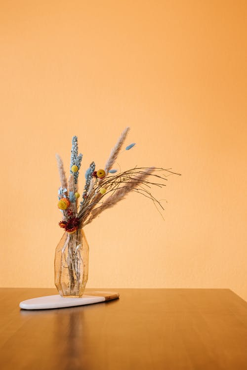 Room with wooden table with glass vase with dried flowers and plants on stand near yellow wall