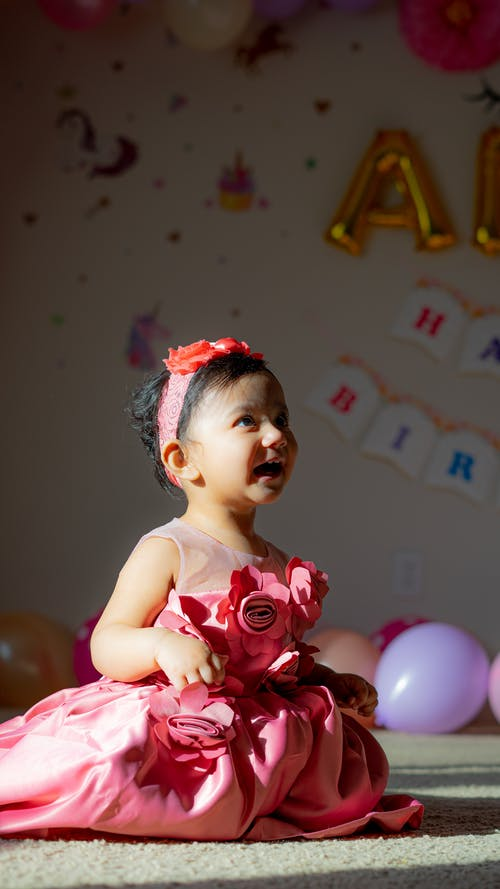 Full body side view of cheerful African American girl in pink dress and headband sitting on floor in light room with garland during holiday celebration