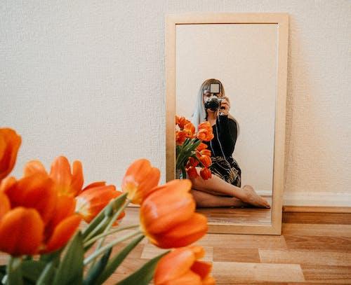 Woman in Black Dress Sitting on Brown Wooden Floor