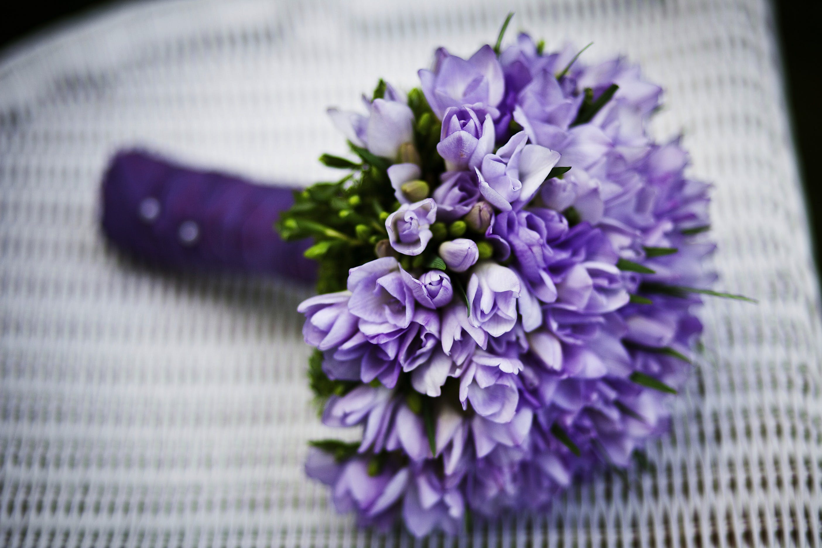 Purple Flower Bouquet on White Woven Chair