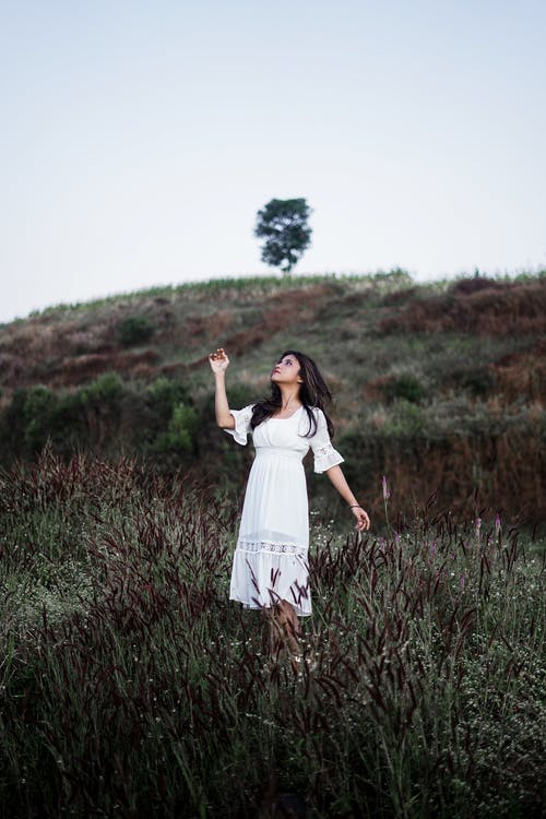 Woman in White Dress Standing on Green Grass Field