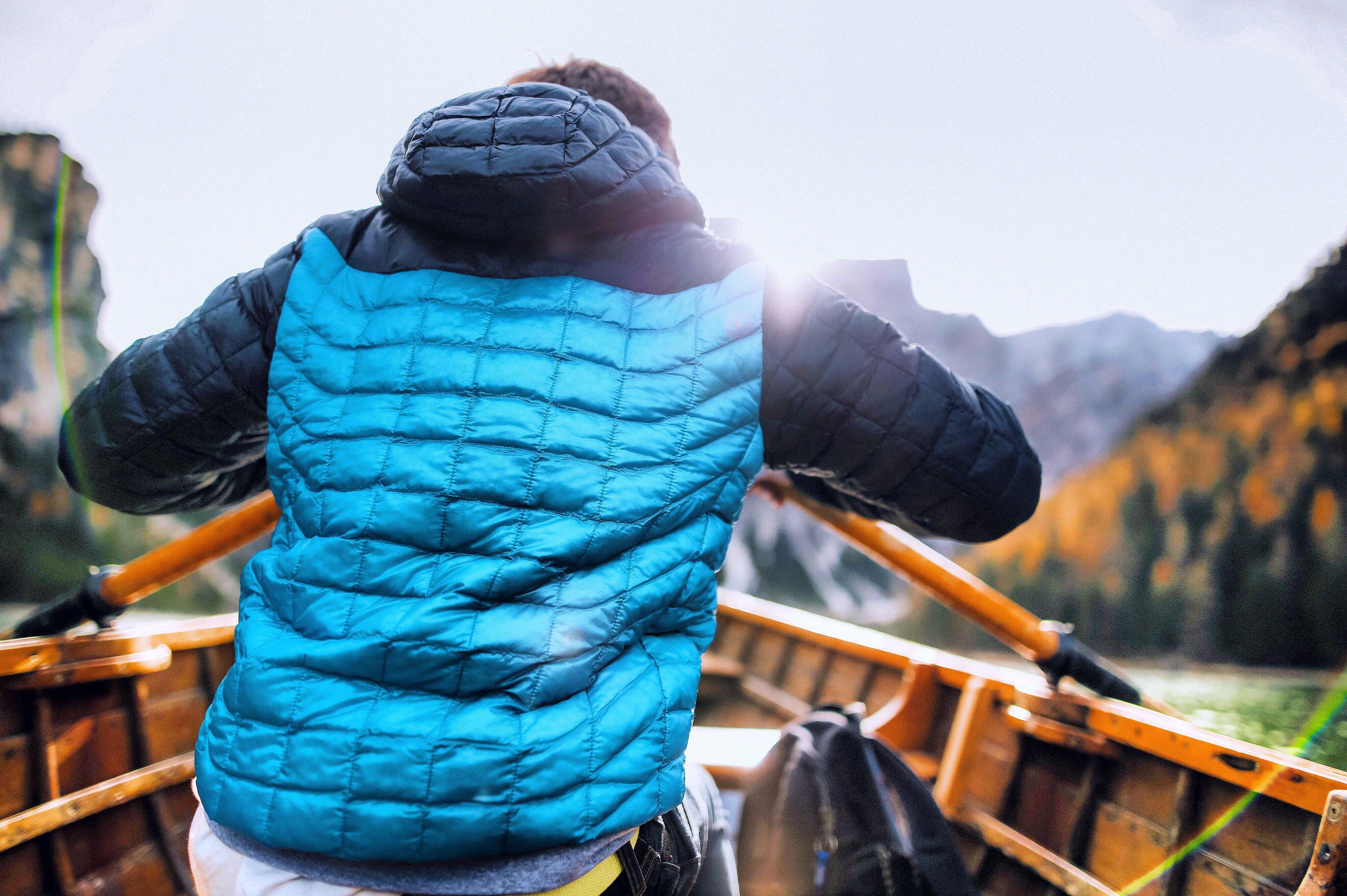 Man in Blue Vest Holding Paddle Sitting Inside Boat