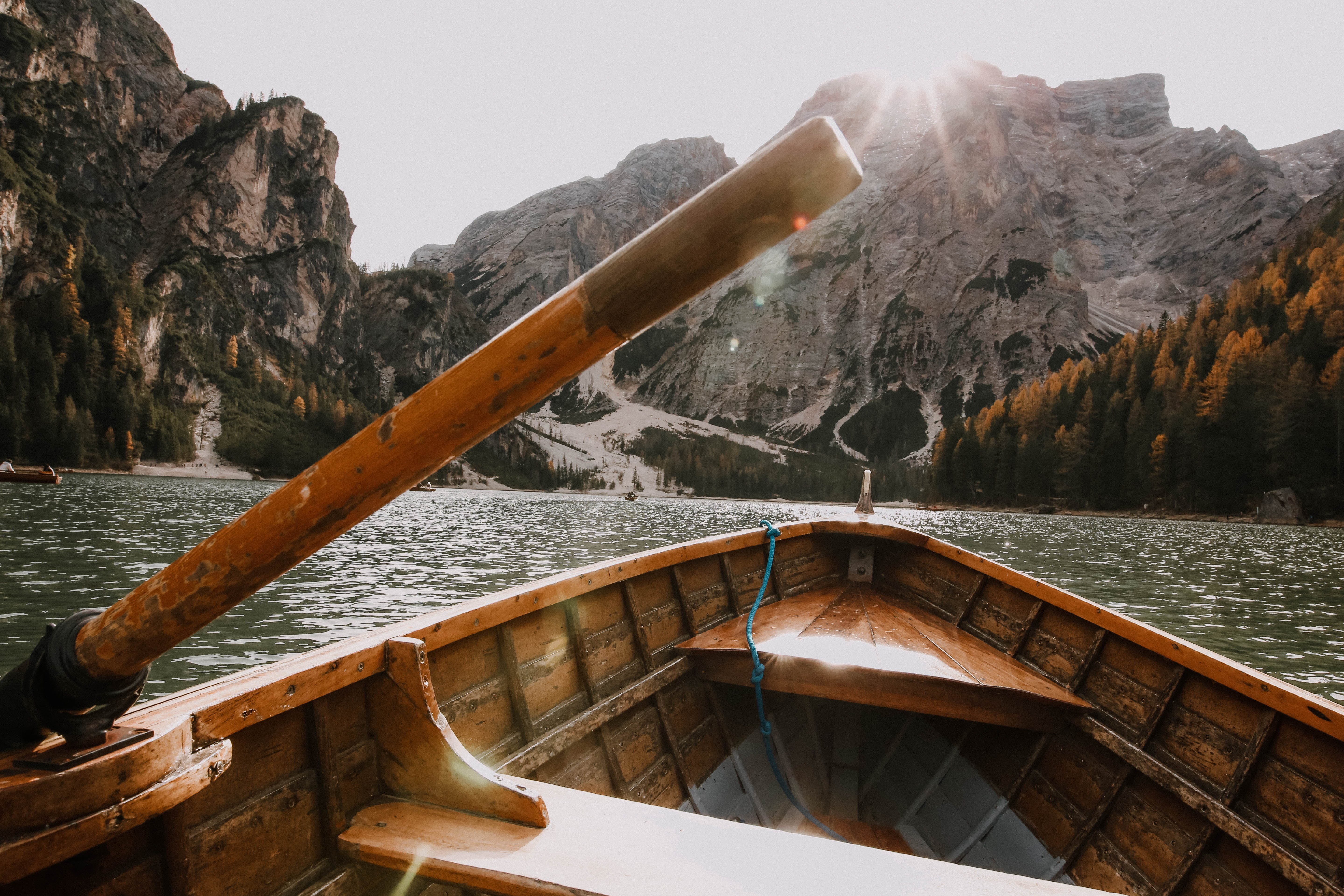 Brown Wooden Canoe on Body of Water Near Mountain